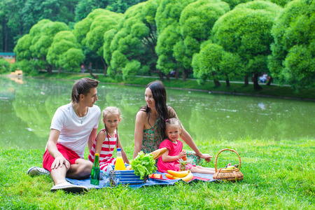 Young family on a picnic by the lake in park photo