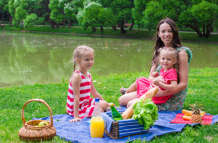 Adorable little girl and happy mother picnicking in the park photo