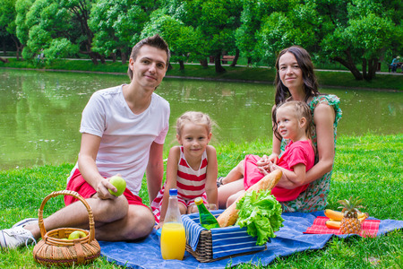 Happy family of four picnicking in the park on summer day photo