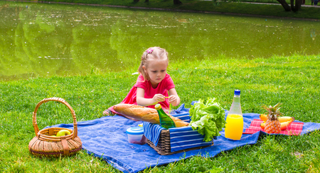 Adorable little girl on picnic outdoor near the lake photo