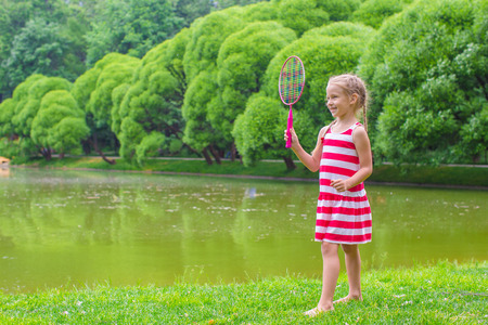Cute little girl playing badminton on picnic photo