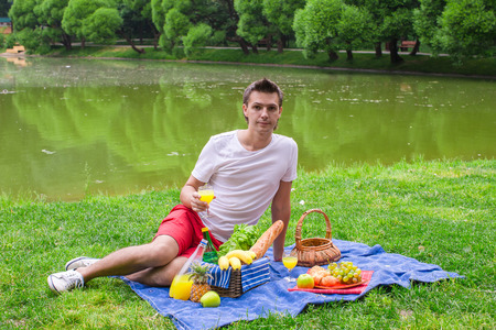 picnicking: Young happy man picnicking and relaxing in the park Stock Photo