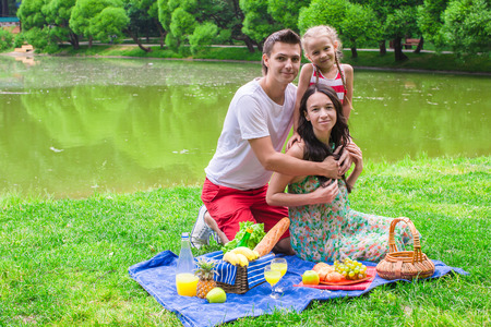 Happy cute family of three picnicking outdoor photo