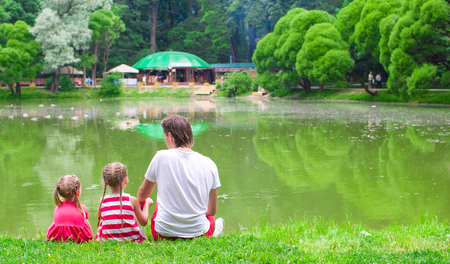 Happy father and little daughers relax near the lake photo
