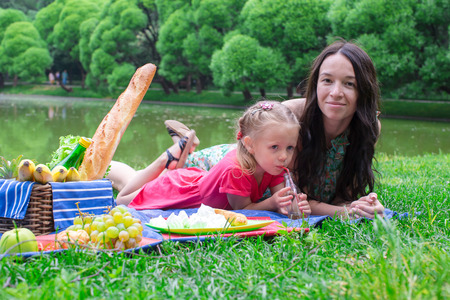 Cute little girl and happy mom picnicking in the park outdoor photo
