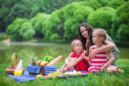 Cute little girls and happy mom picnicking in the park outdoor photo