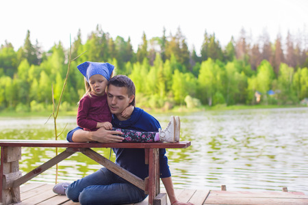 Young father and little girl fishing on the lake photo