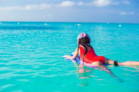 little girl posing: Little cute girl swimming on a surfboard in the turquoise sea