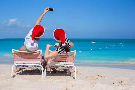 Young happy couple in red Santa hats taking a photo photo
