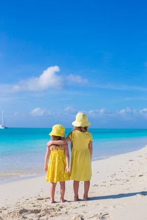 youngbaby: Back view of two little cute girls looking at the sea on white beach Stock Photo