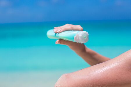 Woman hand putting sunscreen from a suncream bottle photo