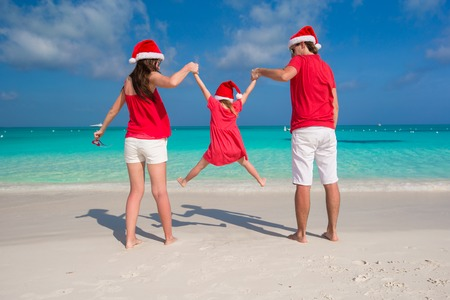 Happy family in Christmas Hats having fun on white beach photo
