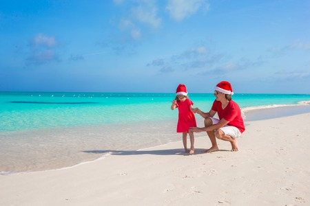 Young father and adorable little daughter in Christmas Hat at tropical beach photo