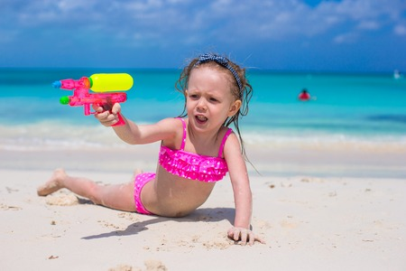 Happy little girl playing with toys at beach during vacation