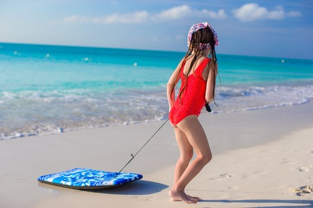 Little adorable girl pulls a surfboard on white shore photo