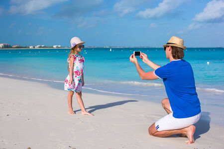 Young father making photo on phone of little girl at beach photo