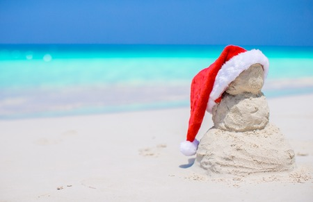 Little sandy snowman with red Santa Hat on white beach photo