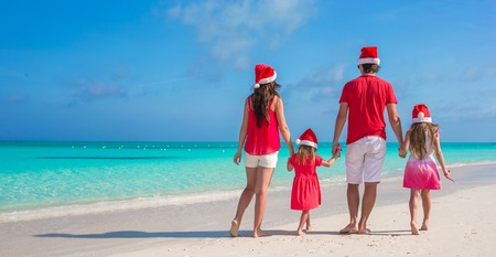 Back view of a young family on tropical beach photo
