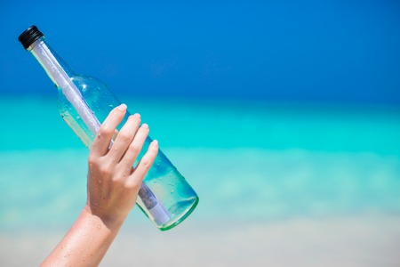 corked: Bottle with a message buried in the sand Stock Photo