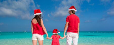 Happy family in Christmas Hats having fun on the beach photo