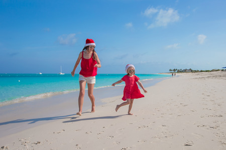 Mother and cute daughter having fun at tropical beach photo