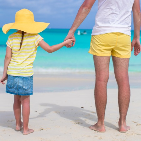 Close up of father and daughter holding hands at beach photo