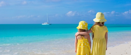 youngbaby: Back view of two sisters looking at the sea on the white beach