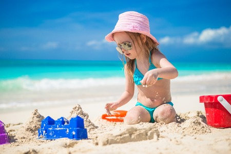 Adorable girl playing on the beach with white sand
