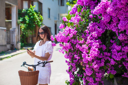 Young beautiful woman with phone near flower tree photo