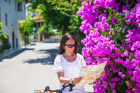 Beautiful girl read the map of the island with a bicycle photo