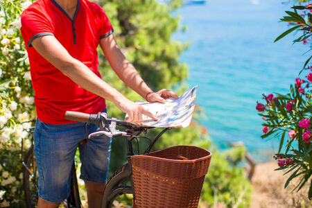 Young traveling man with map of the island with a bicycle photo