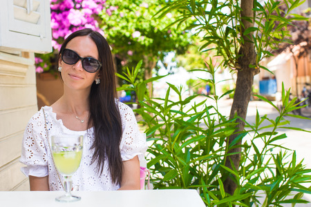 Young pretty girl in outdoor cafe enjoy her vacation photo