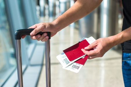 Closeup of man holding passports and boarding pass at airport photo