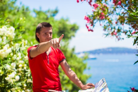 Young traveling man with map of the island photo