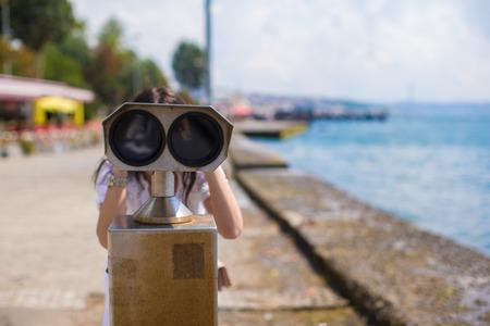 mujer mirando el horizonte: Bella joven mirando con monedas de binoculares en el estrecho del B�sforo