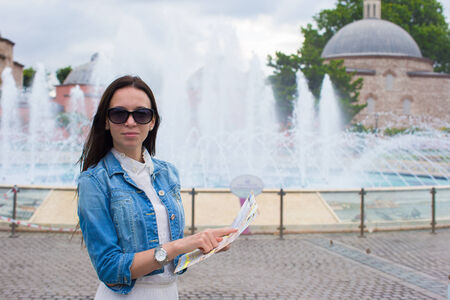 Young beautiful caucasian woman reading a map photo