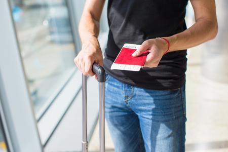 Man holding passports and boarding passport at airport waiting the flight photo