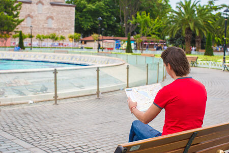 Portrait of young caucasian traveling man reading a map photo