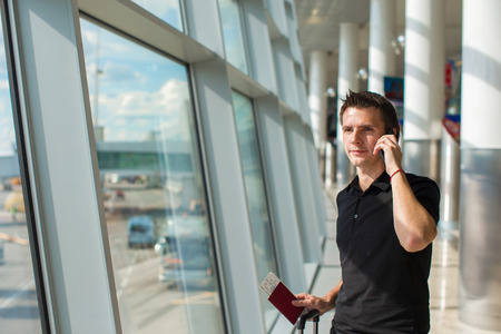 Businessman talking on smartphone walking inside in airport photo