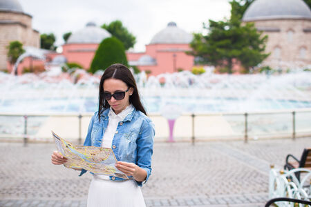 Young pretty woman tourist in big city with map photo