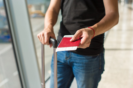 Man holding passports and boarding pass at airport while waiting the flight photo