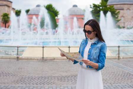 Young beautiful traveling woman with map of city in hands photo