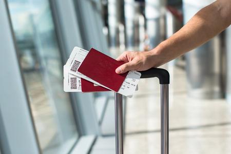 flight: Closeup of man holding passports and boarding pass at airport Stock Photo