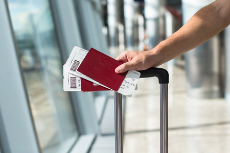 Closeup of man holding passports and boarding pass at airport Standard-Bild