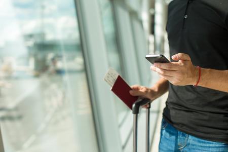travellers: Man holding cell phone, passports and boarding passport at airport waiting the flight Stock Photo