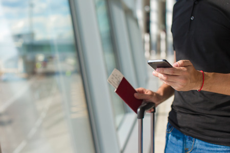 Man holding cell phone, passports and boarding passport at airport waiting the flight Banque d'images