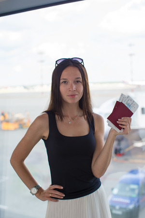 Woman holding passports and boarding pass at airport waiting the flight photo