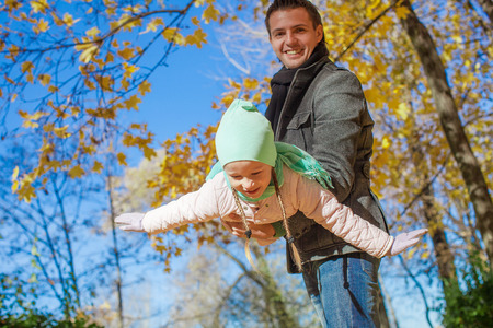 Little girl with happy father having fun in autumn park on a sunny day photo