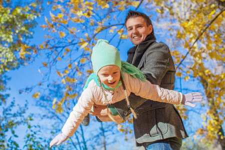 Little cute girl and happy father having fun in autumn park on a sunny day photo