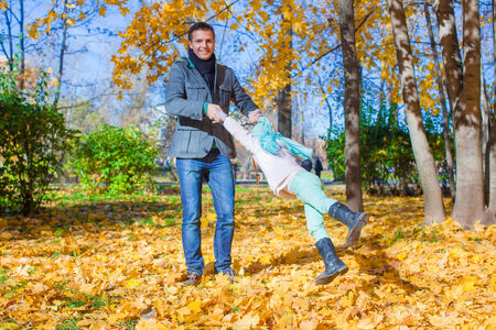 Adorable little girl with happy dad having fun in autumn park on sunny day photo